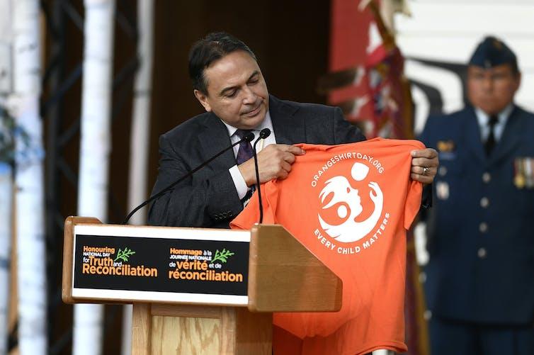 A man holds up an orange shirt at a podium.