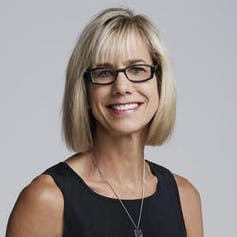 A woman with blonde hair and glasses smiles