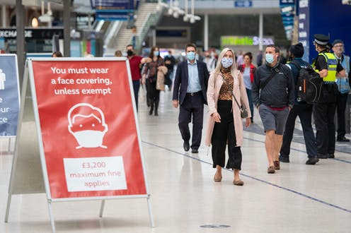 Two men and a woman walk past a sign saying 'You must wear a face covering, unless exempt' at a railway station