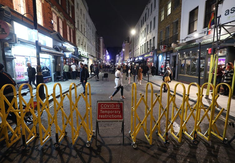A yellow barrier bars access to a London street.