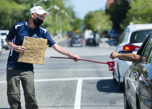 A homeless man uses a self-made contraption to properly physical distance while panhandling for money during the COVID-19 pandemic in Toronto.