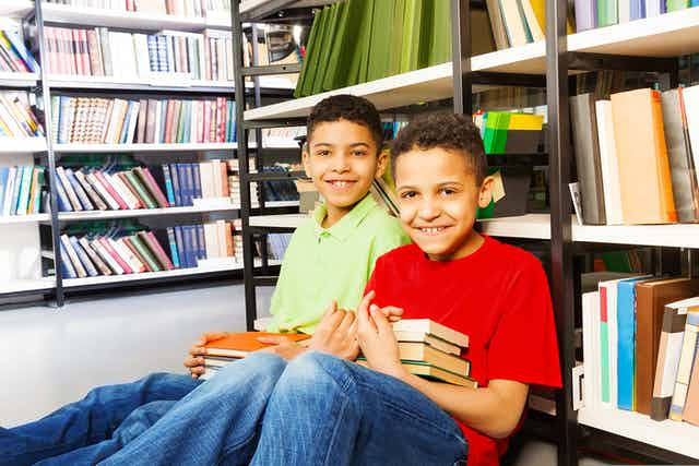 Two boys sitting on floor in a library, holding books and leaning against book shelf.