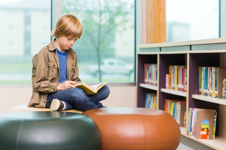 Boy sitting cross legged on round stool in library and reading.
