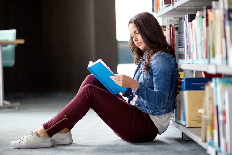 Girl reading in a library, leaning against book shelf.