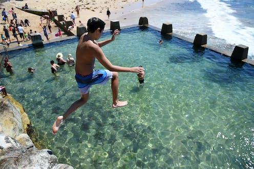 A boy jumps into an ocean pool in Sydney.