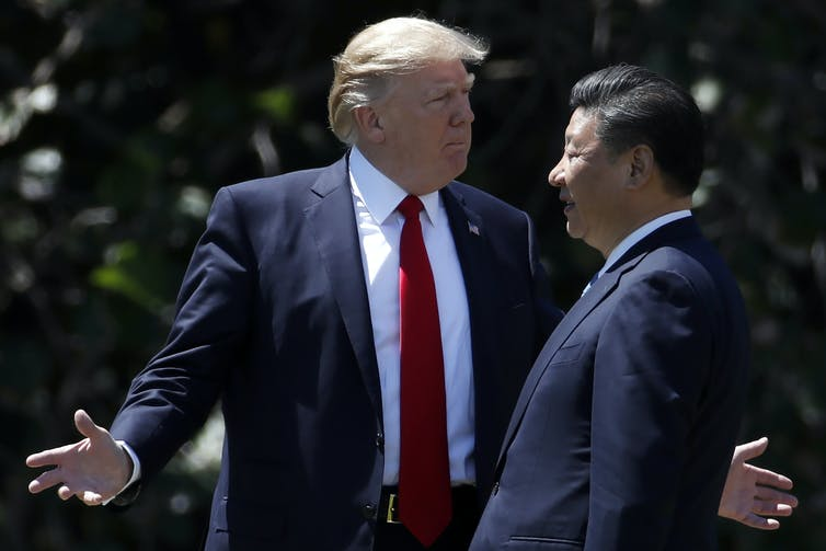 Donald Trump talks to Xi Jinping with arms outstretched