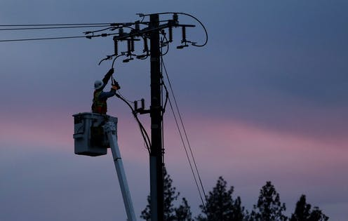 A linesperson works on a electrical utility pole