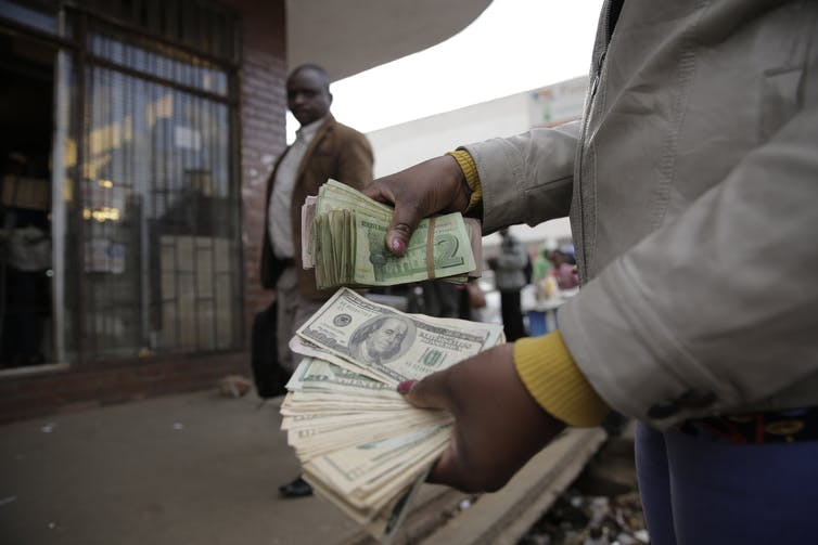 A foreign currency trader holds Zimbabwe US dollars in Harare, Zimbabwe,