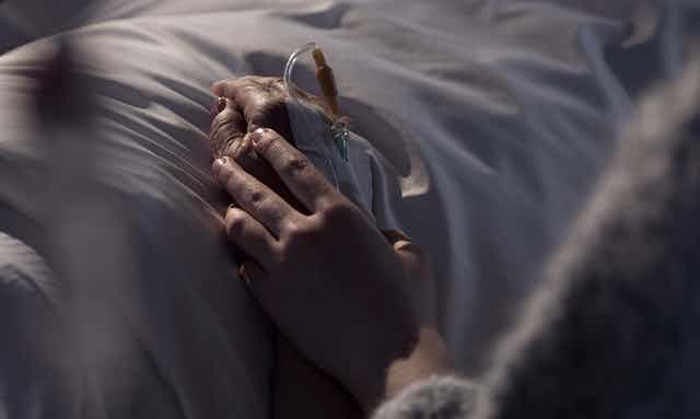 Woman holding hand of a patient