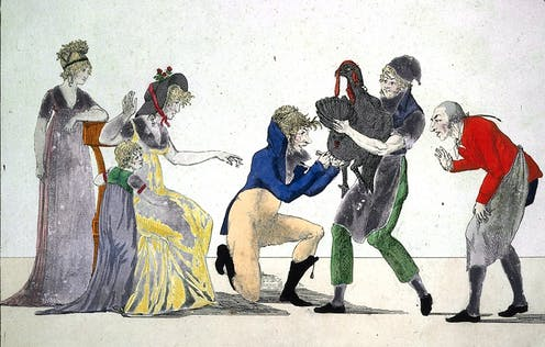 A man holds a turkey as a doctor puts a lance in its leg. A man observes on the right, and two well-dressed women and a child watch on the left.