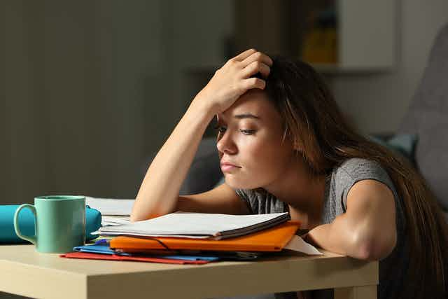 Girl sitting at study desk, looking tired.