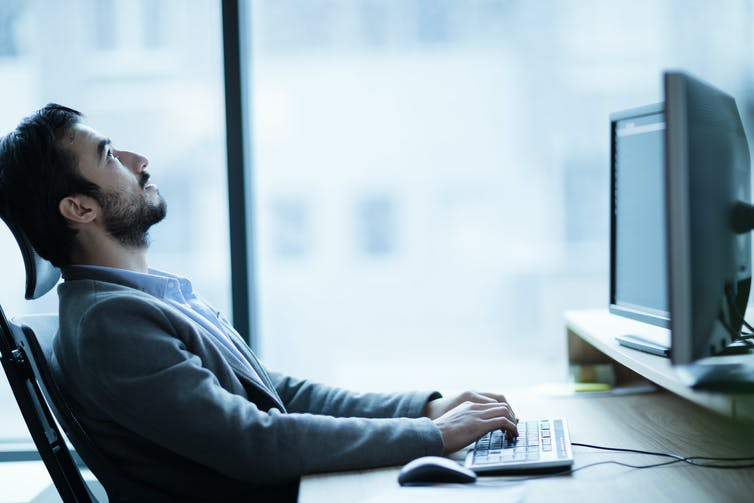 Stressed man leaning back from computer