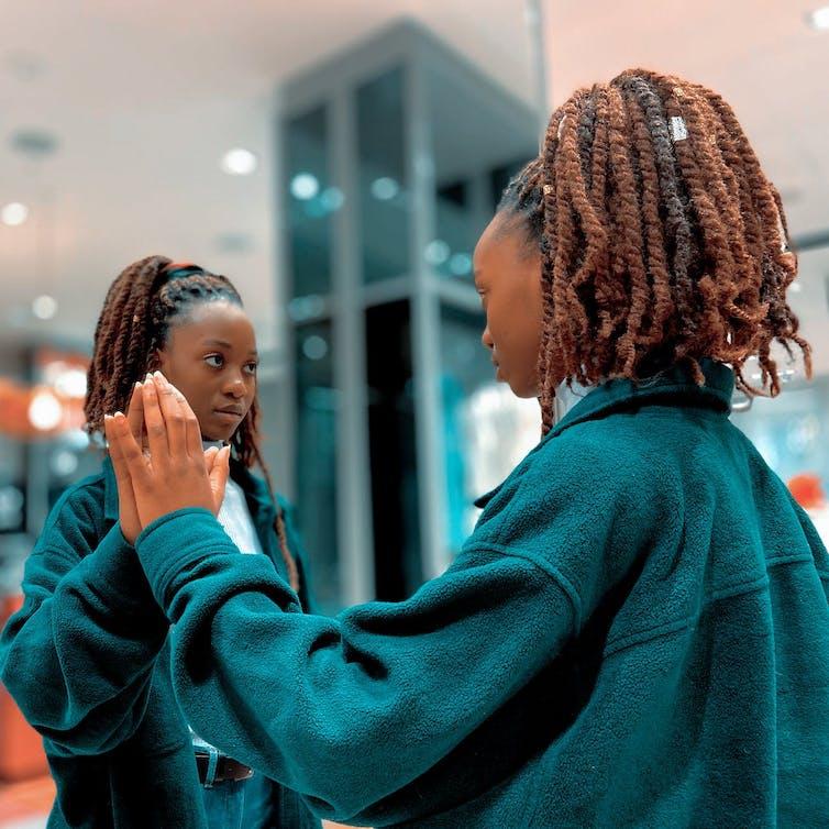 Girl in denim jacket looking in the mirror.