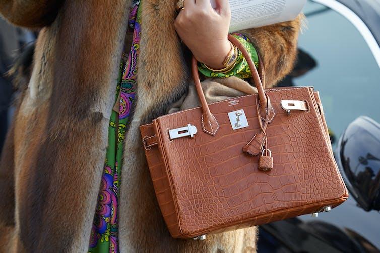 A woman wearing a fur coat holds a brown crocodile skin handbag.