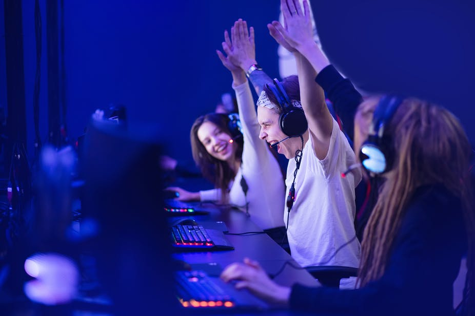 Esports gamers celebrating a victory at their desks