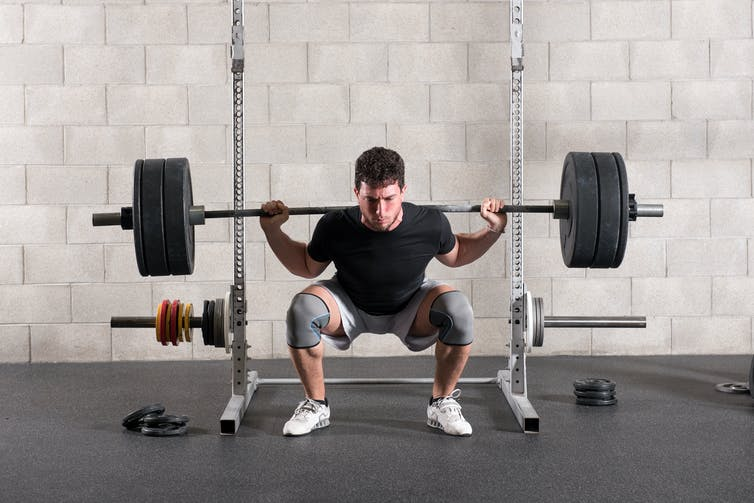 Man performs a squat with a barbell on his back.