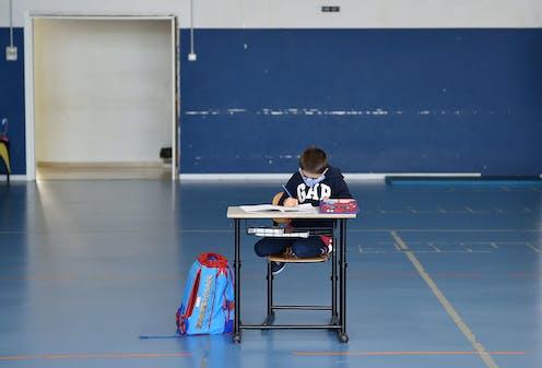 Child alone at school desk wearing mask