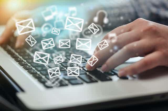 Sobrecillos de correo saliendo de un ordenador mientras alguien escribe en el teclado.
