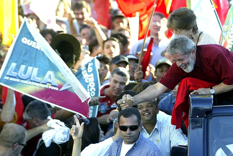 Lula da Silva on car greeting crowd of supporters holding flag with his name on it.