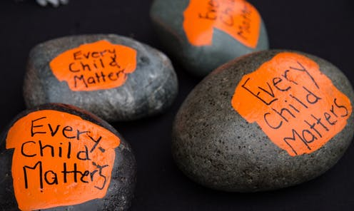 Rocks painted to say 'every child matters.'