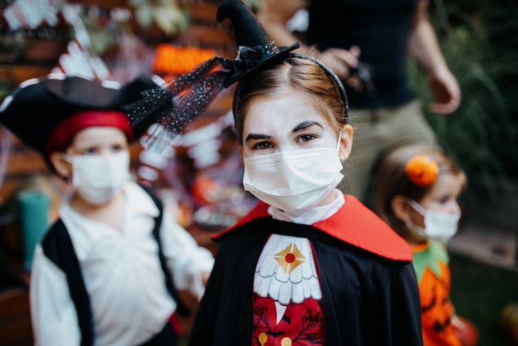 While trick-or-treating, everyone in your family must wear a mask and socially distance from others.
