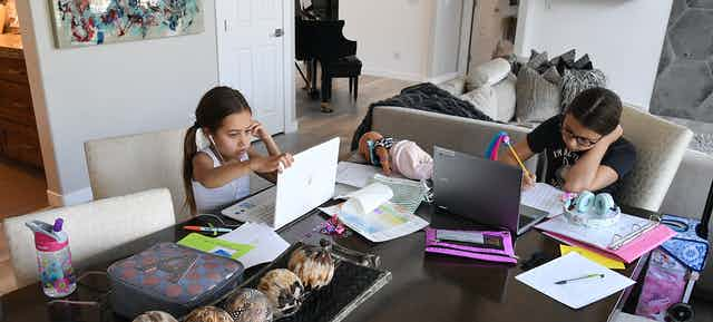 Two sisters do remote education at their dining room table.