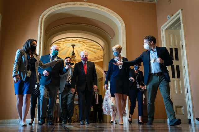 McConnell in a mask, walking through the Capitol surrounded by reporters recording him on cell phones