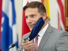 Federal Immigration Minister Marco Mendicino removes his face mask.
