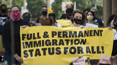 Women wearing masks carry a sign reading Full & Permanent Immigration Status for All