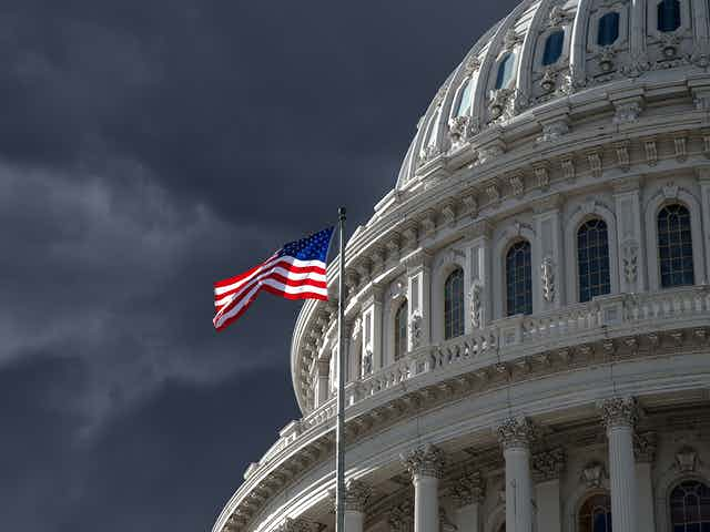 The US Capitol, with stormy skies and an American flag