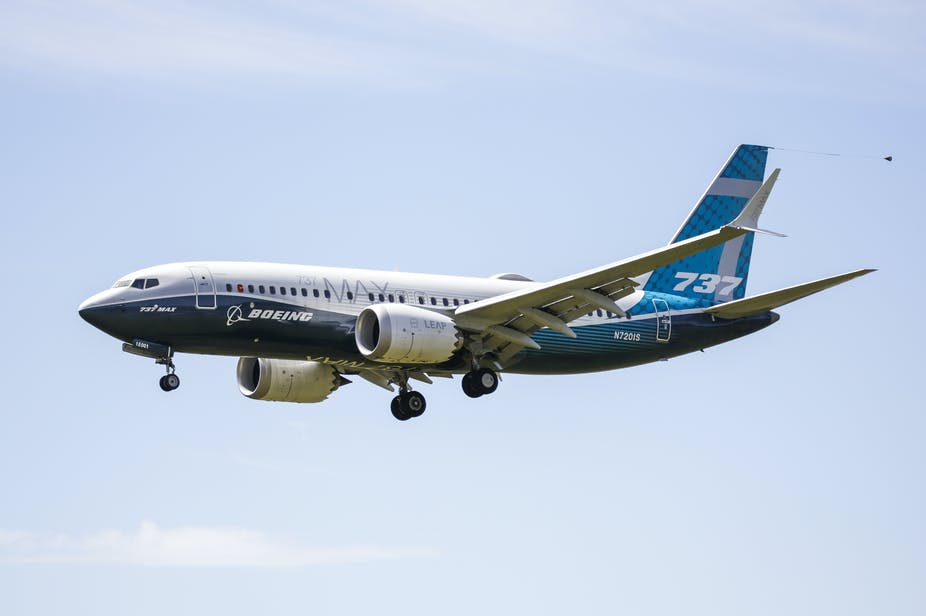 A Boeing 737 Max flying with its landing gear coming down.