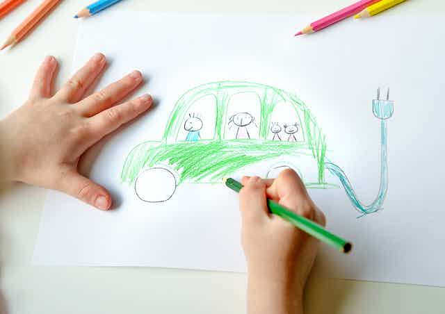 A child drawing an electric car