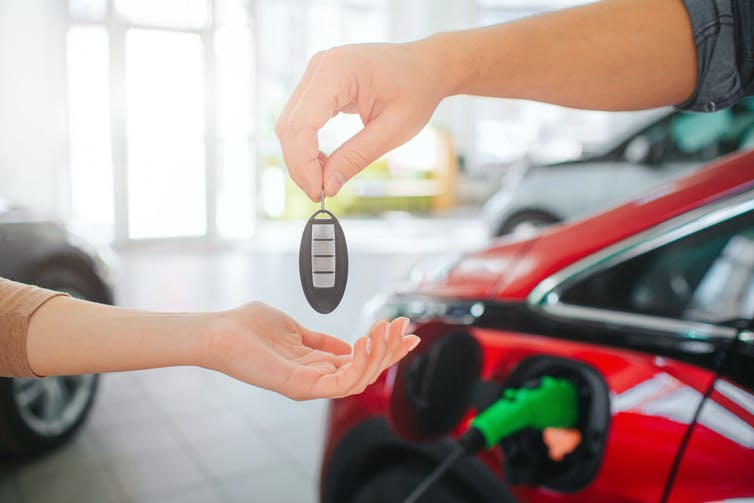 Hands transferring keys to an electric car.