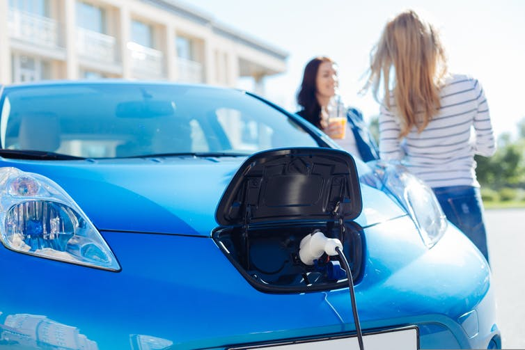 Two women standing next to an electric car.