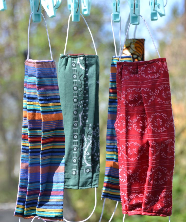 Four cloth masks hanging on a clothesline.