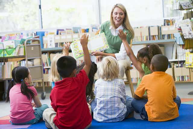 White teacher reading book to children sat on floor, hands up to answer question