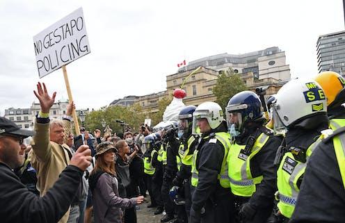 Protestors and police line up in Trafalgar Square.