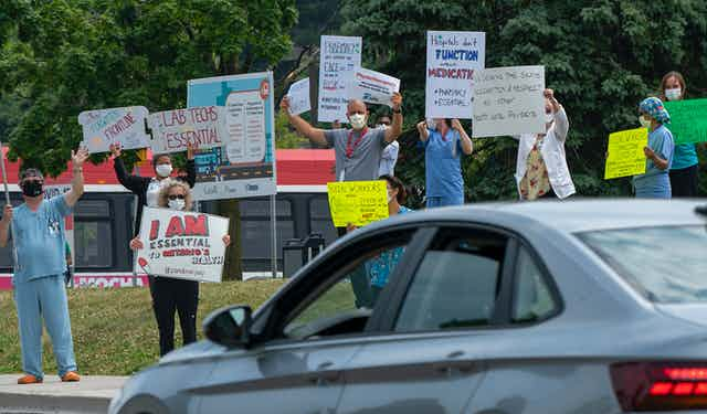 Health-care workers wearing masks and carrying signs wave at a passing car.