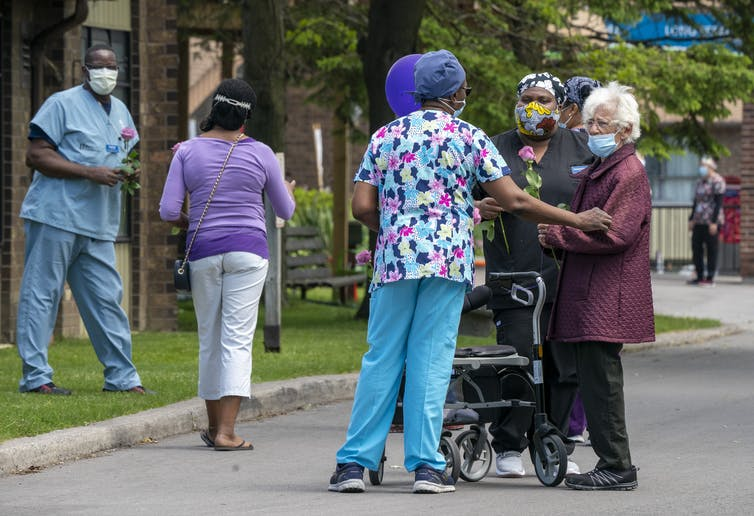 An elderly woman with a walker and wearing a mask chats with long-term workers wearing masks.