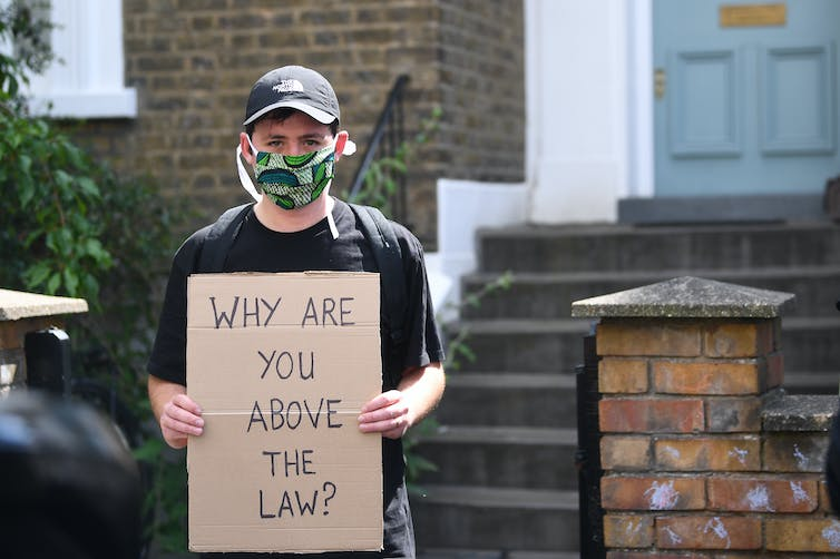 A protestor with a sign reading 'why are you above the law?'