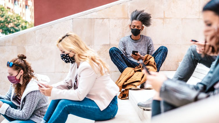 Students sit on university steps looking at smartphones and wearing masks.