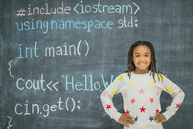 A Black girl with braids stands in front of a chalkboard with computer coding written in various colors