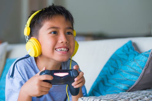 A smiling young Asian boy wearing yellow headphones holds a game controller
