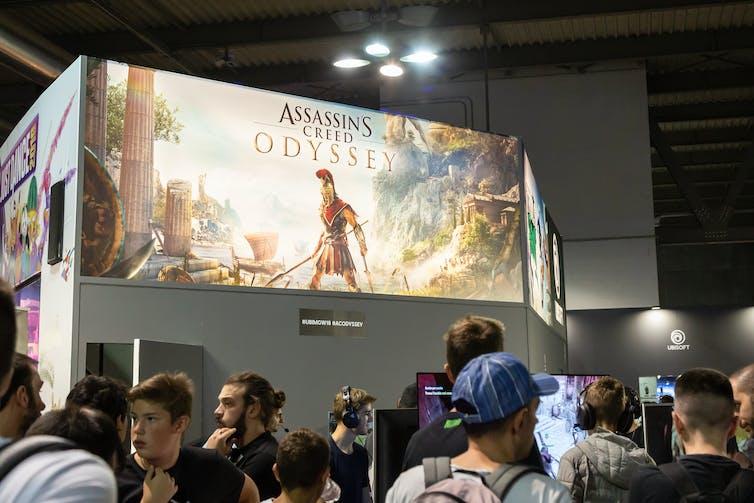 یک بیلبورد غول پیکر که یک گلادیاتور از بازی ویدیویی Assassin's Creed را نشان می دهد ، به جمعیت زیادی مشرف است.