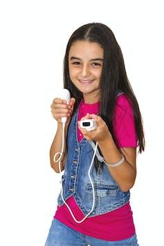 یک نوجوان جوان با تی شرت صورتی و جلیقه جین که دارای کنترل کننده Wii است.