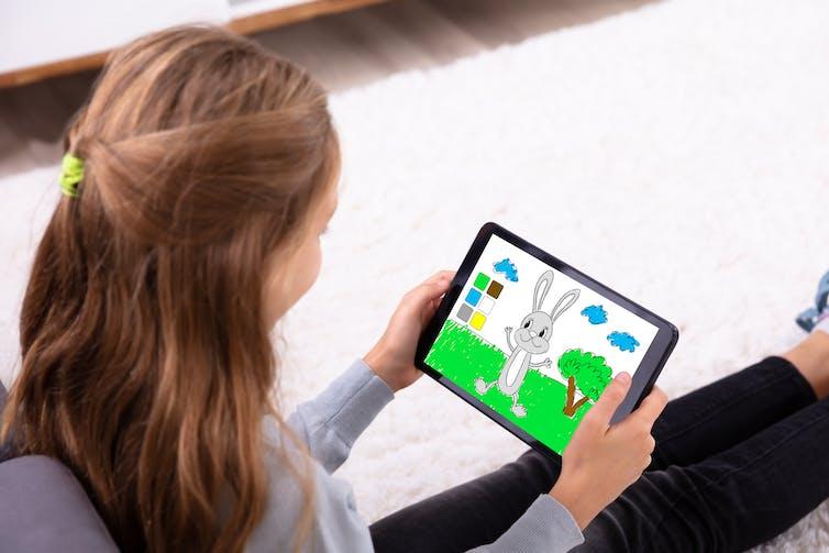 نمای جانبی دختر جوانی که روی صفحه لوحی با خرگوش کارتونی در دست دارد