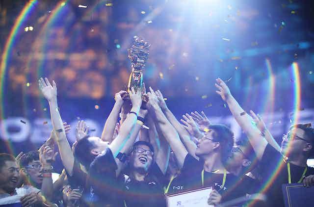 students celebrate holding prize aloft