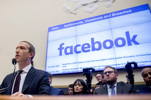 Mark Zuckerberg stands in front of a microphone with a screen showing the facebook logo behind him and the words Settlements, Violations and Breaches