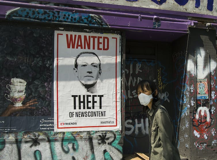 A woman wearing a surgical mask walks past a wanted poster of Mark Zuckerberg