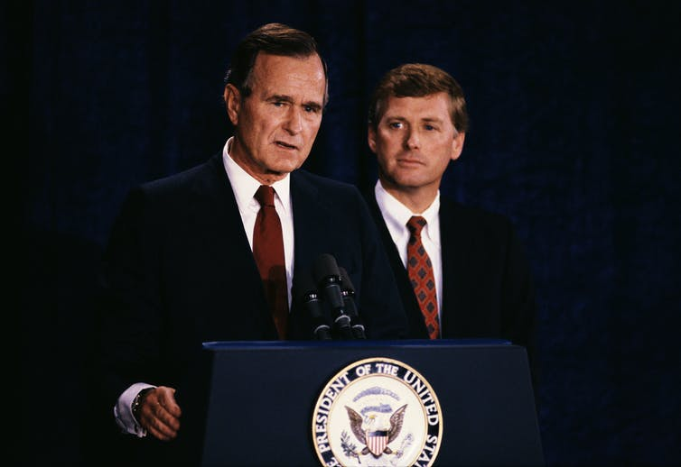Bush and a youthful Quayle stand at a lectern in dark suits with red ties